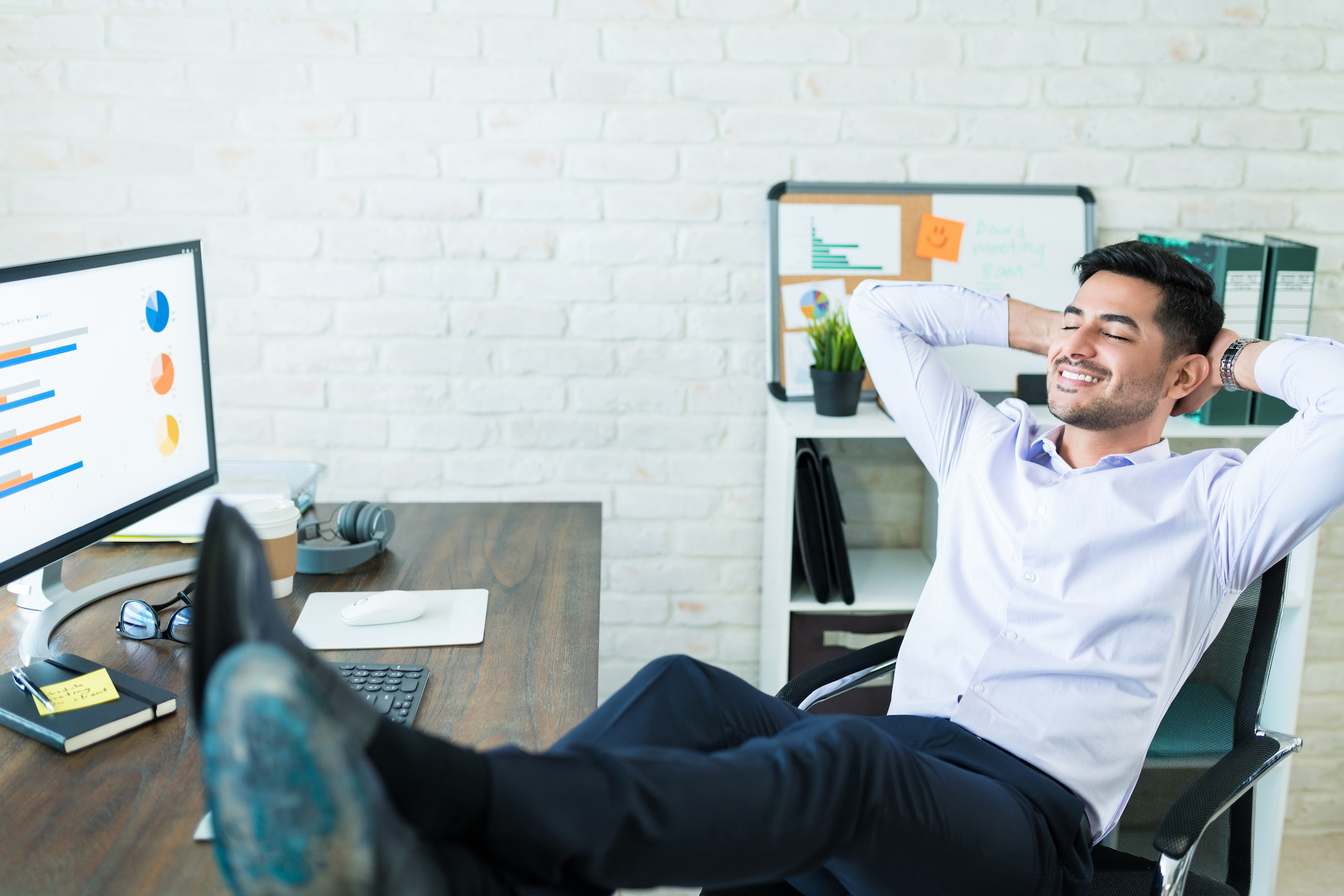 Full length of young male Latin sales freelancer relaxing with feet up on desk